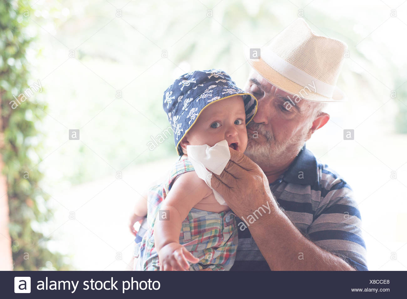 Grandfather wiping baby boy's chin with handkerchief - Stock Image