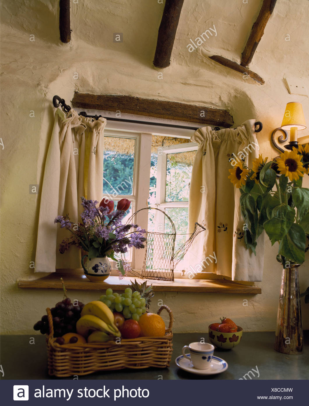 Small window with cream curtains on portiere rods above ...