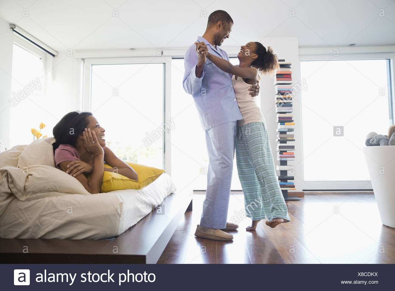 Father and daughter dancing in bedroom - Stock Image