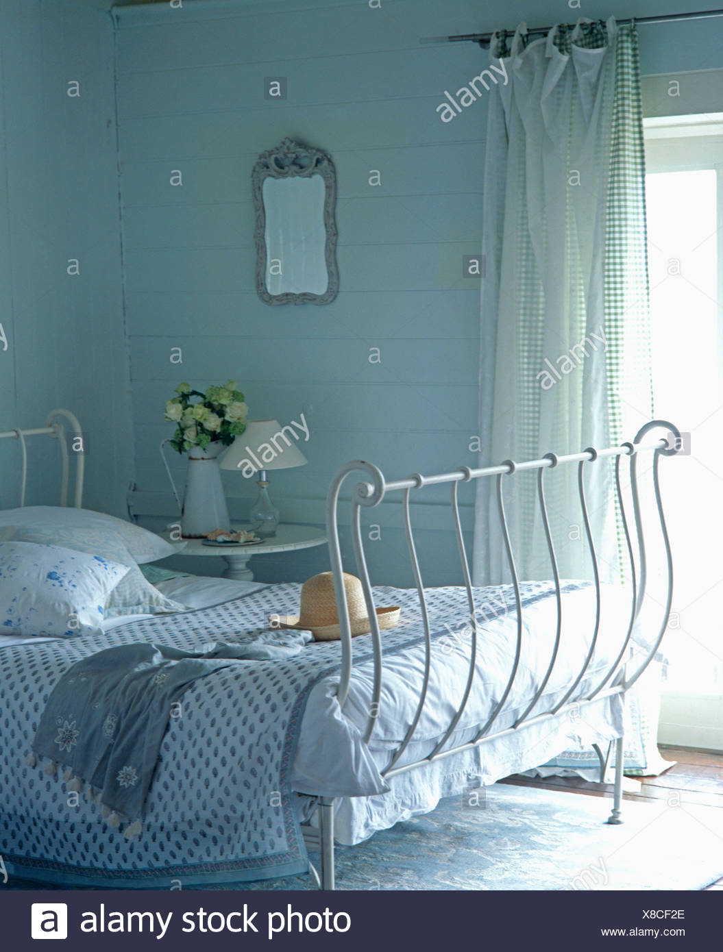 White Wrought Iron Bed With Pale Blue Quilt In Cottage Bedroom With Checked And White Voile Curtains Stock Photo Alamy
