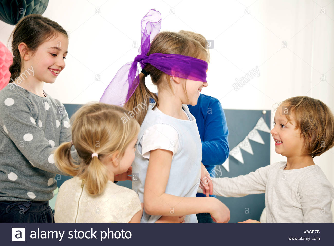 Children on birthday party playing Blind Man's Bluff, Munich, Bavaria, Germany - Stock Image