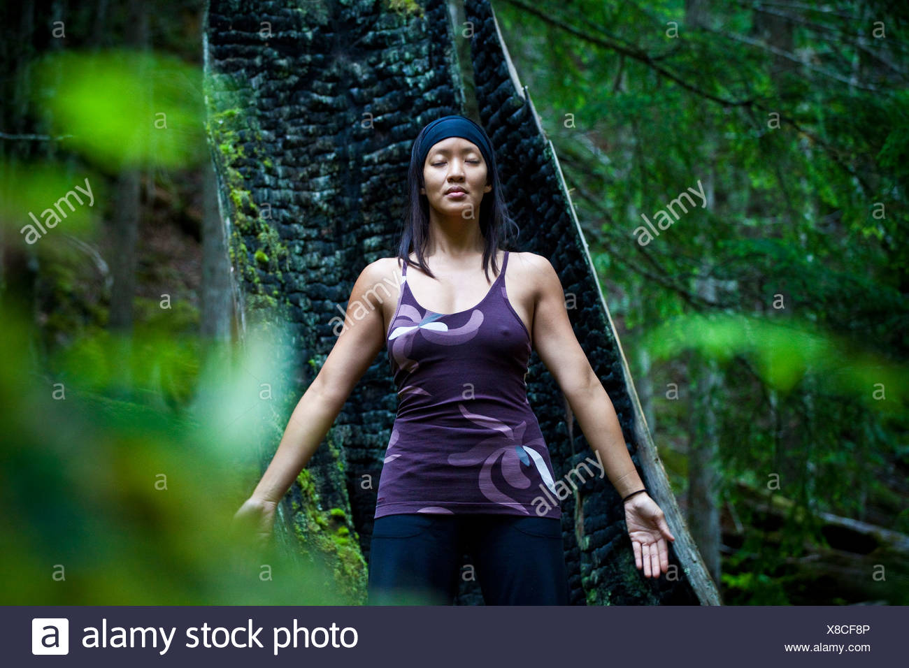 A woman practices yoga near the Clearwater River, Clearwater, British Columbia, Canada - Stock Image