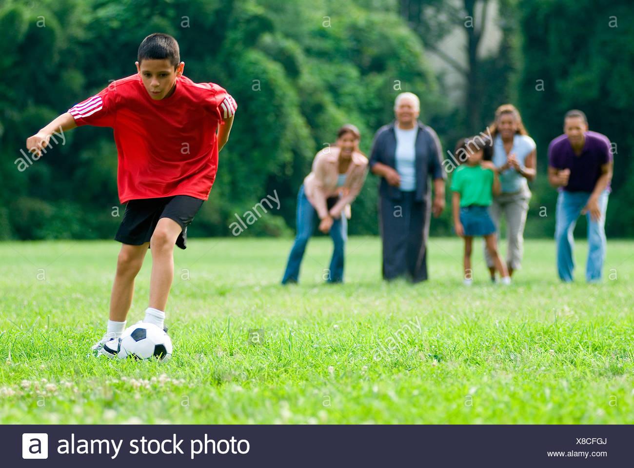 Young Hispanic boy kicking soccer ball as family watches - Stock Image