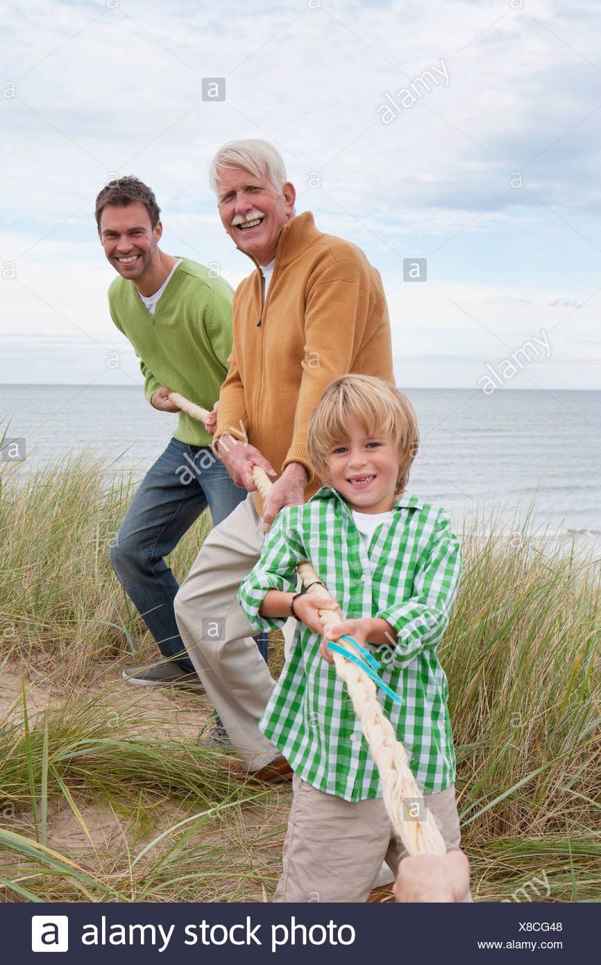 Male Family Members Taking Part In Tug Of War Match On Beach - Stock Image