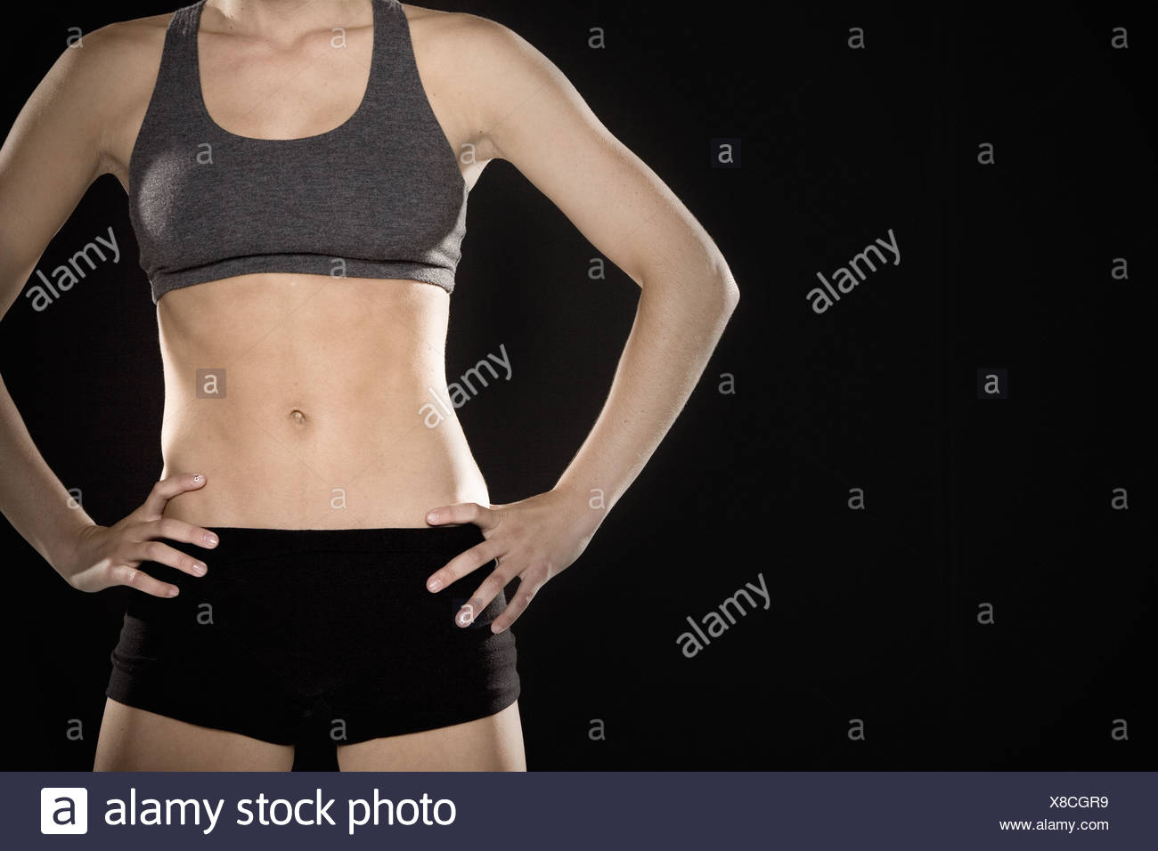 Woman in athletic gear with hands on hips - Stock Image