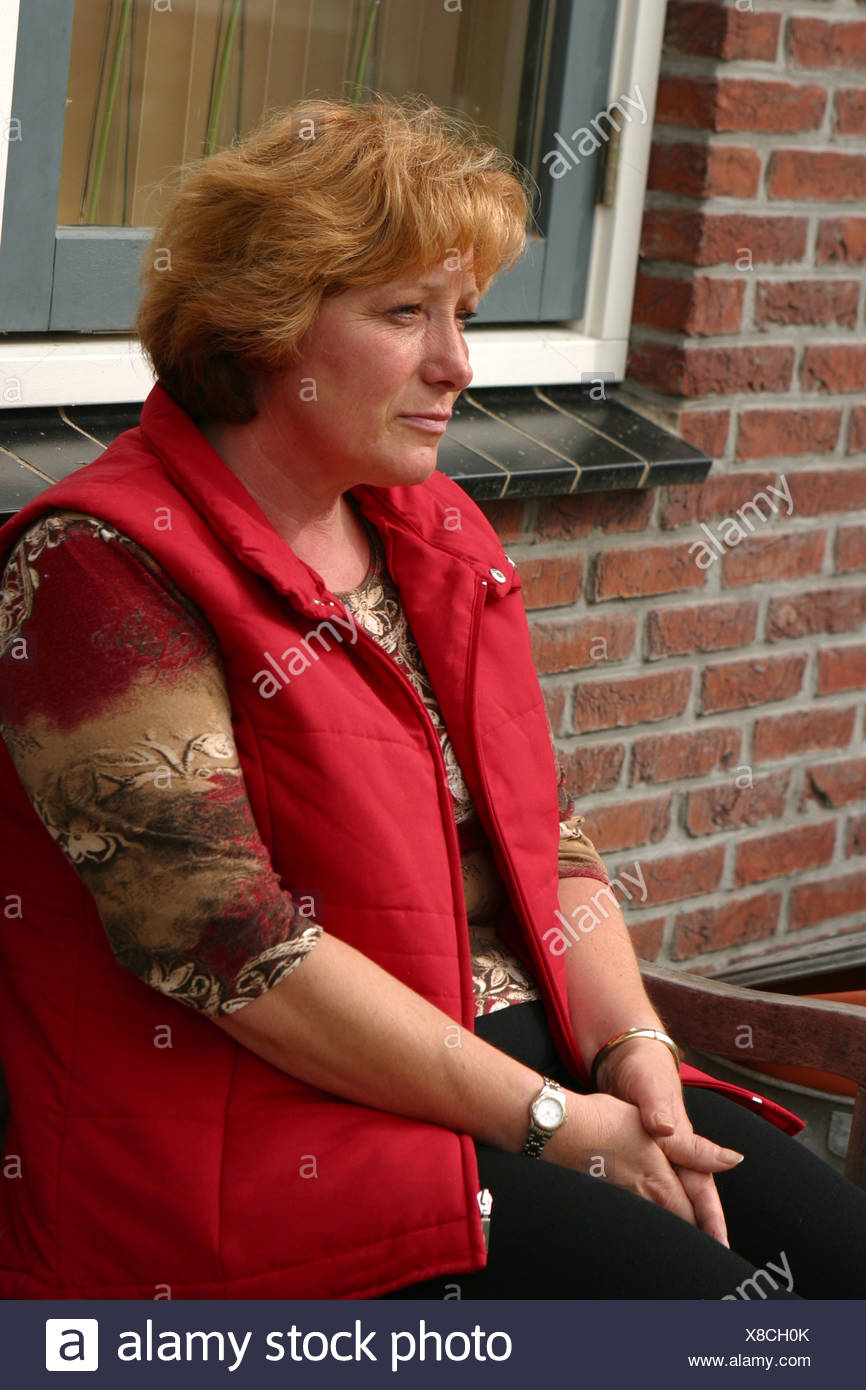 Mature woman 50 sad or worried outdoors pensive mood retreat on front porch bench - Stock Image