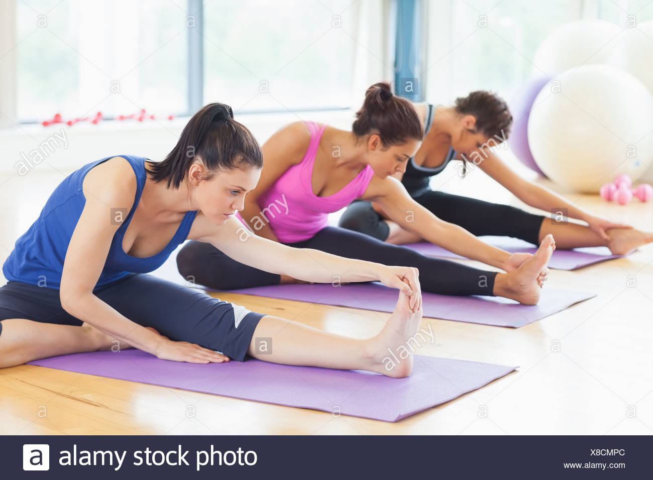 Fit class stretching legs on mats at yoga class Stock Photo