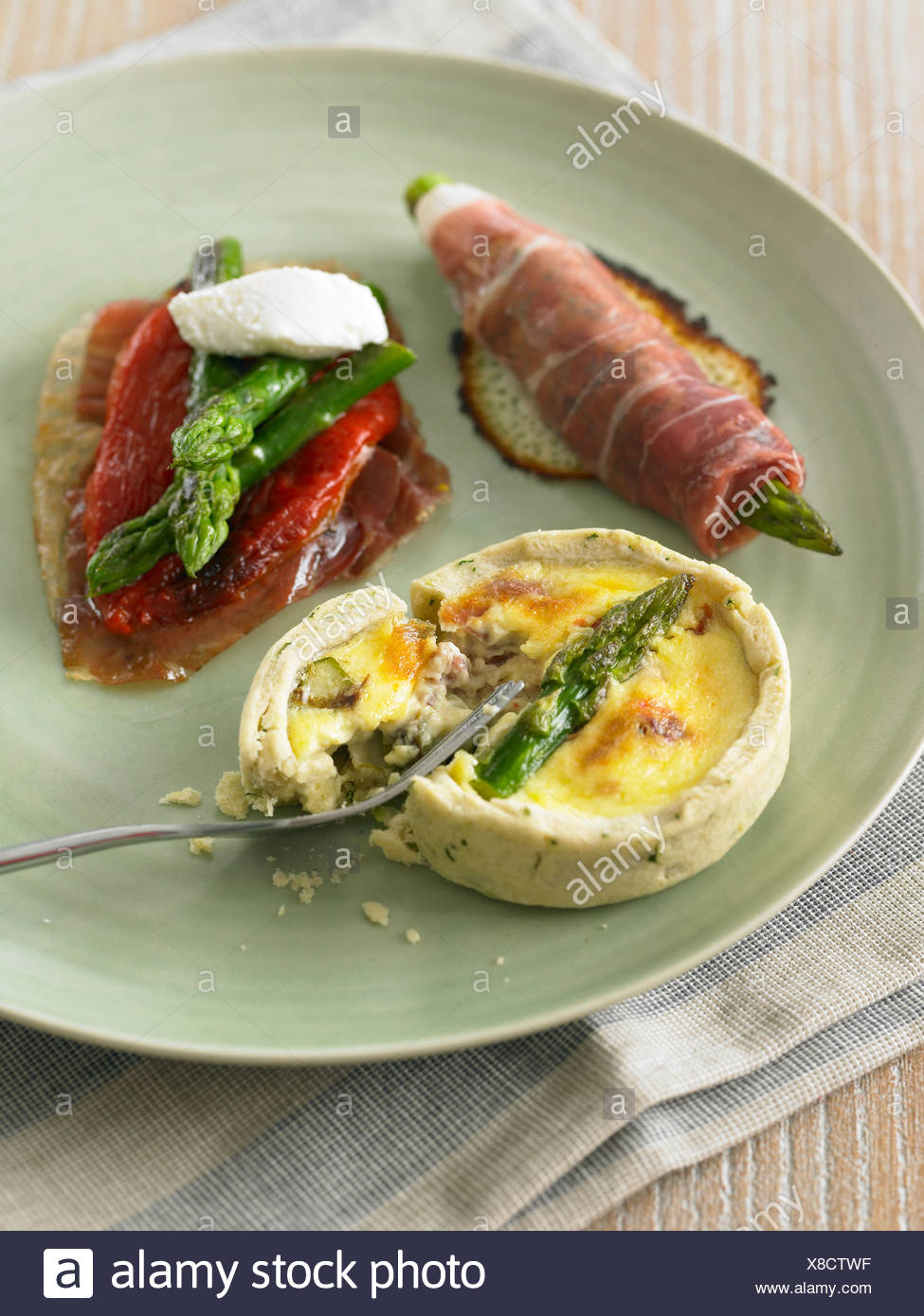 Trio of starters on plate, asparagus wrapped in smoked parma ham, asparagus tart, and parma ham with red peppers and asparagus - Stock Image