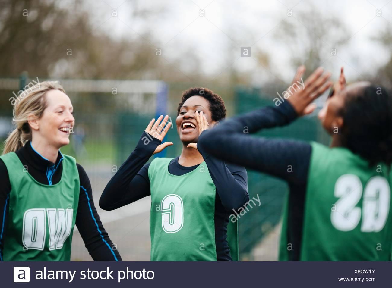 Adult female netball team celebrating win on netball court - Stock Image