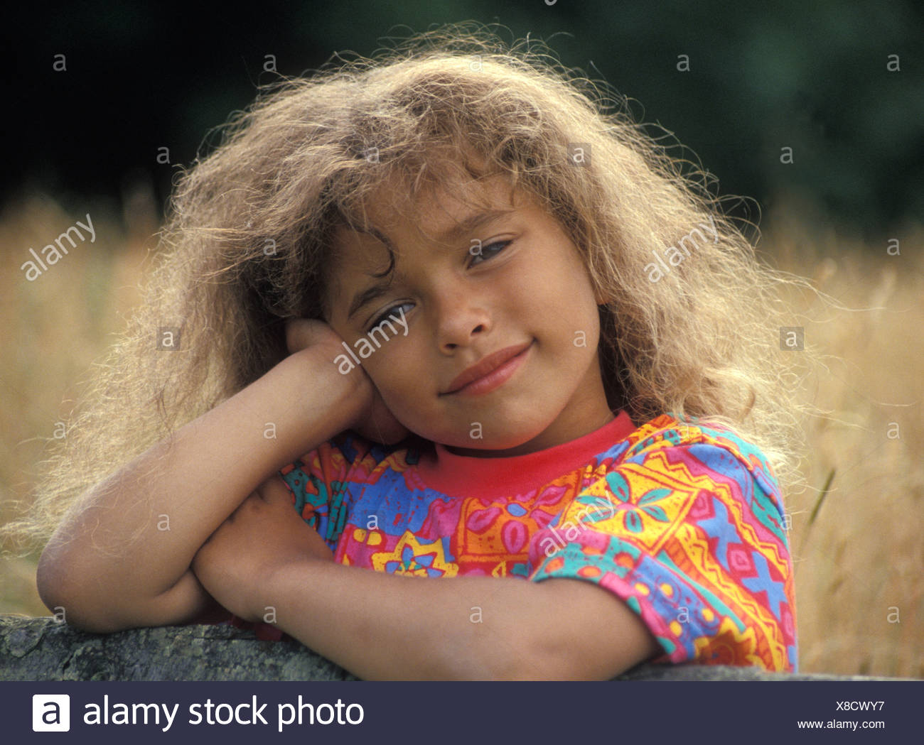 Portrait Dark Skinned Little Girl With Long Curly Hair Posing In