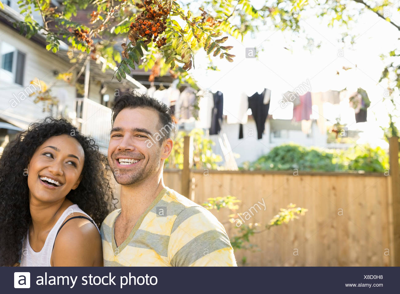 Portrait of laughing couple in sunny backyard - Stock Image
