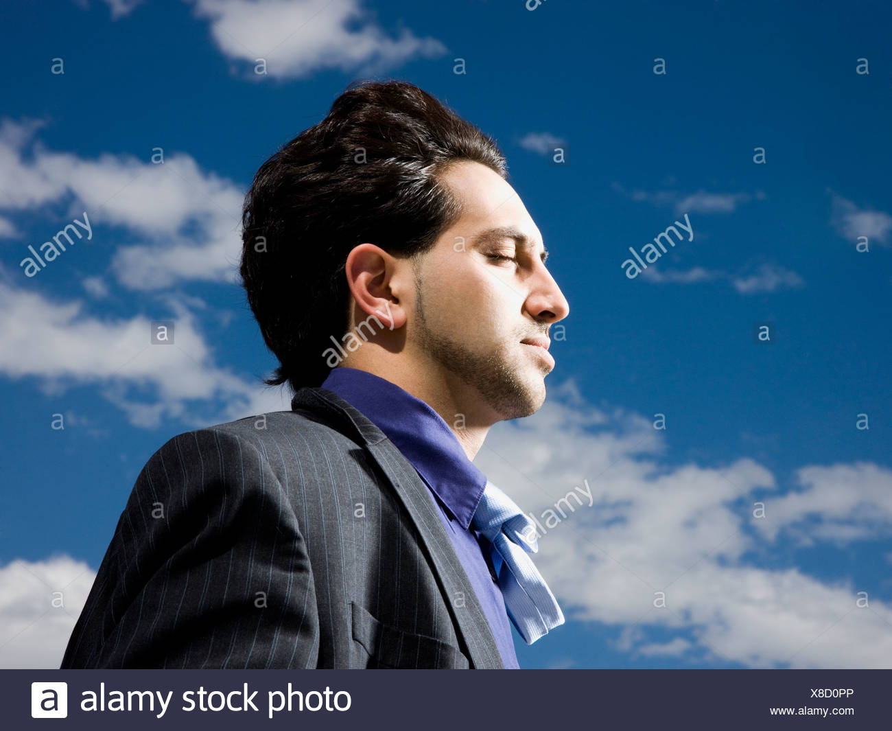 man in a suit with head tilted back - Stock Image