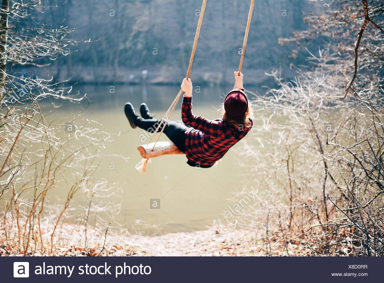 Rear View Of A Girl Swinging Against Calm Lake - Stock Image