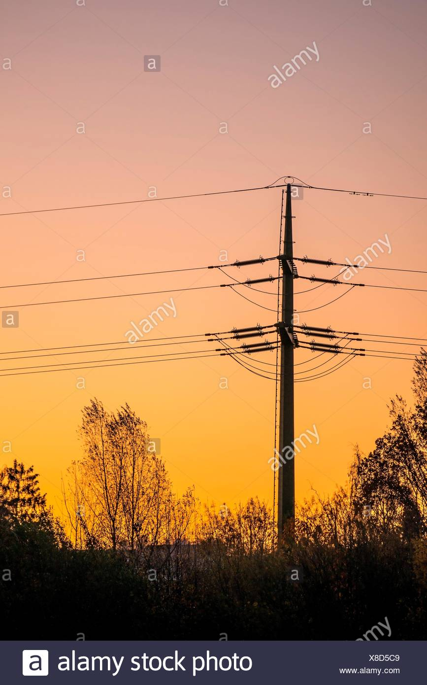 sunset with afterglow and power mast in Germany - Stock Image