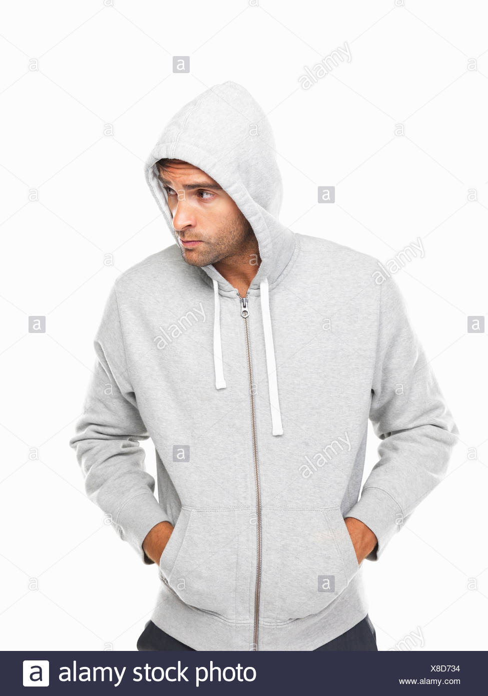0dae2538 Young man in hoodie standing with hands in pockets Stock Photo ...