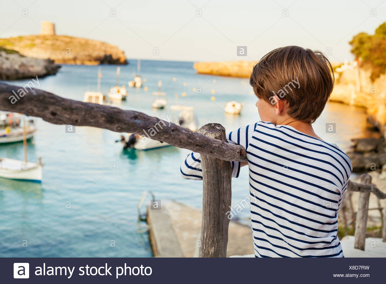 Spain, Menorca, Boy (6-7) looking at seaside view - Stock Image