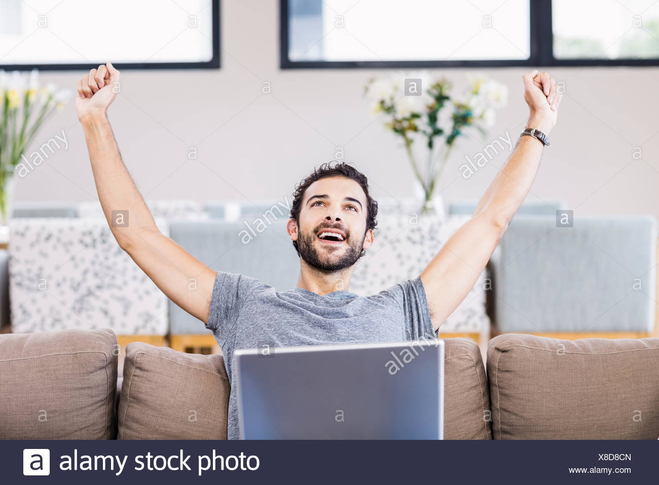 Handsome man rejoicing with laptop on legs - Stock Image