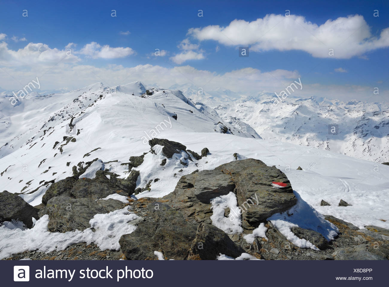 Marker of a ski tour route on metamorphic primitive rocks with footprints in the snow, Zillertal main crest at back, Tux Glunge - Stock Image