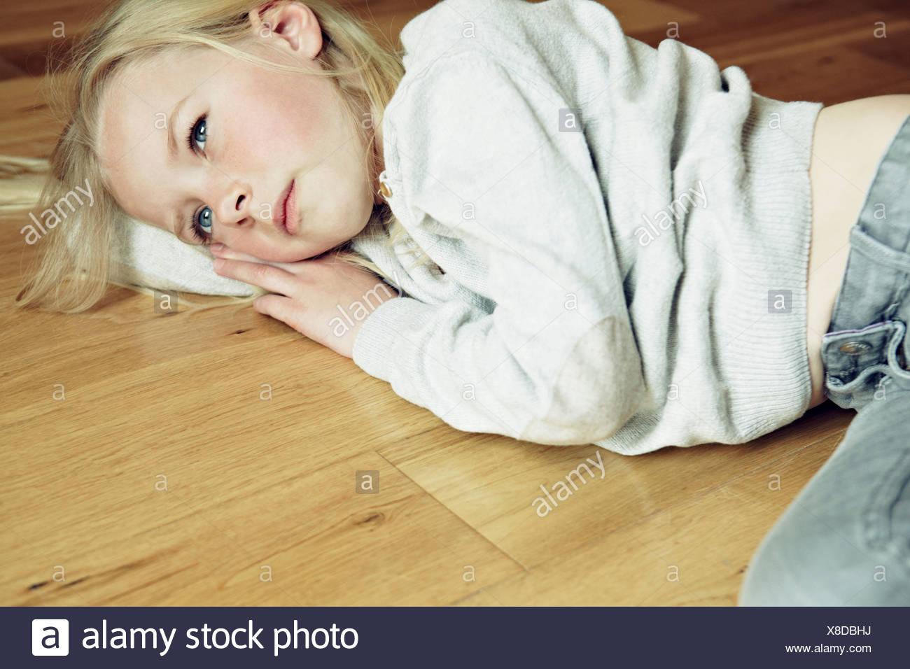 Young girl lying on wooden floor, looking away - Stock Image