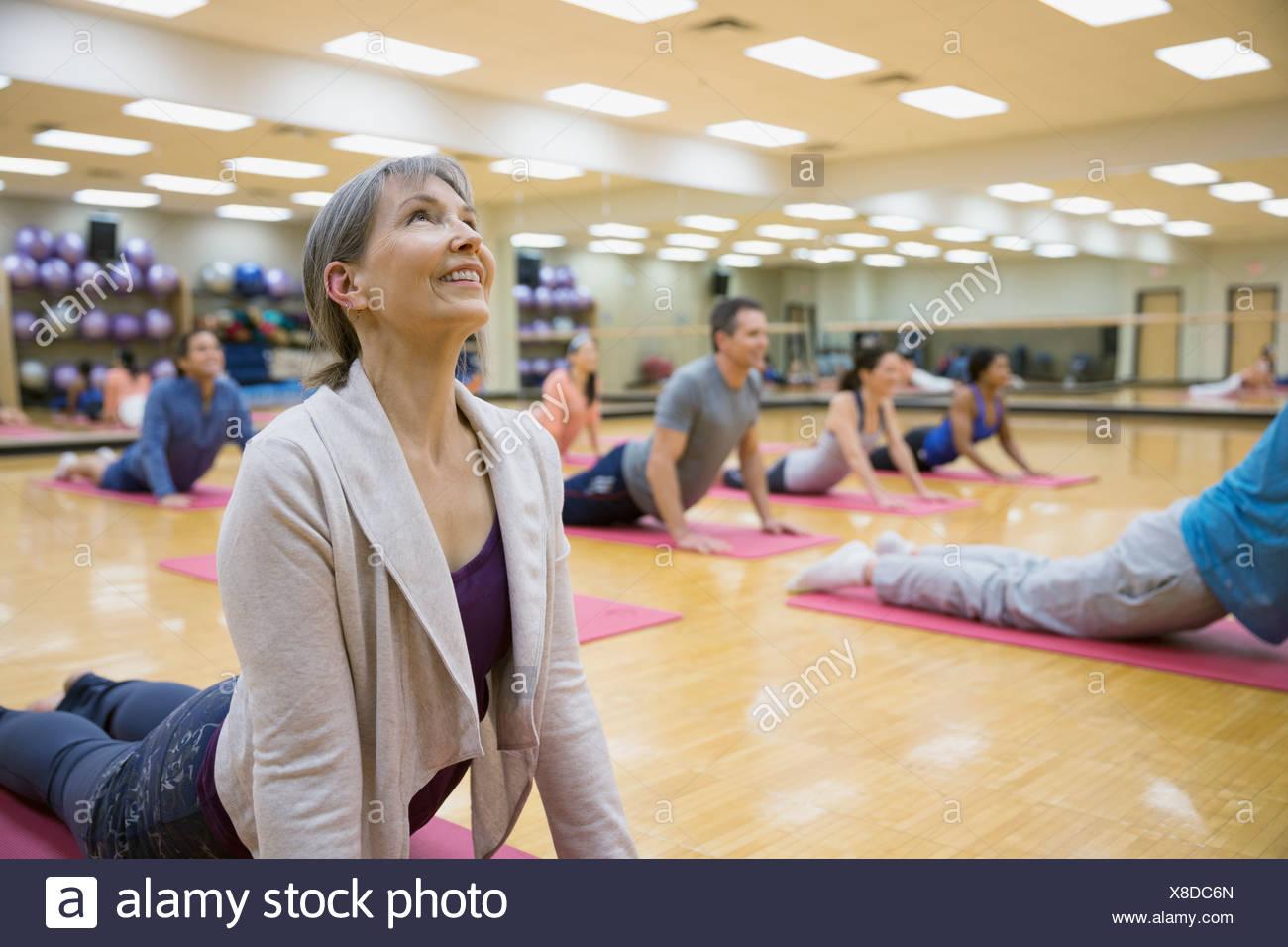 Group practicing upward facing dog in yoga class - Stock Image