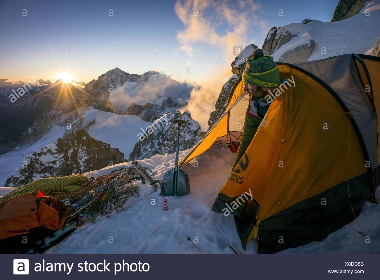 A mountaineer emerges from a tent at Camp III as the sun sets with Gamalang Razi in the distance. - Stock Image