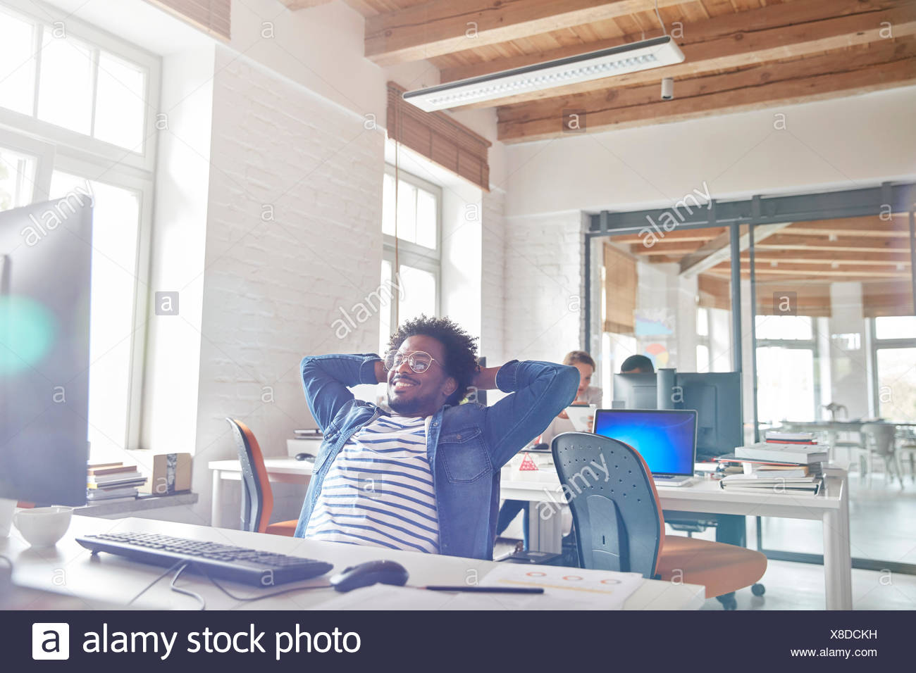 Confident businessman leaning with hands behind head at computer - Stock Image