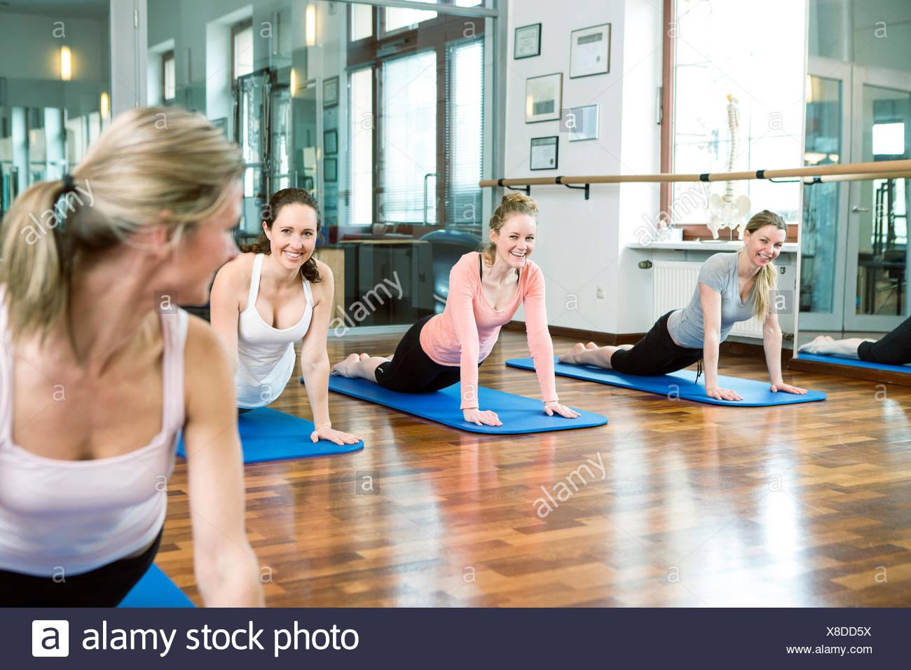 Group of women doing Pilates exercises - Stock Image