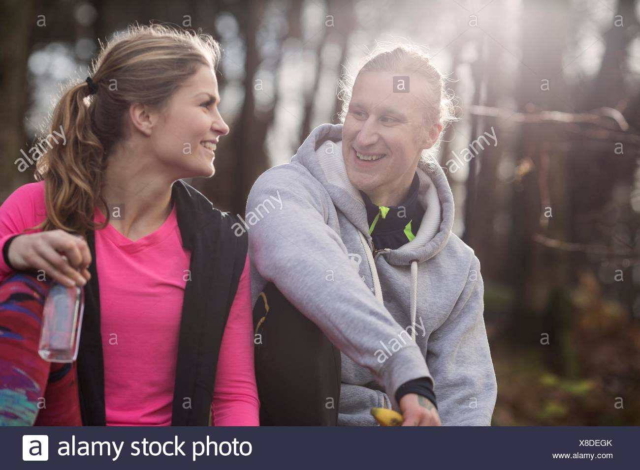 Couple wearing sports clothing holding water bottle sitting face to face smiling - Stock Image