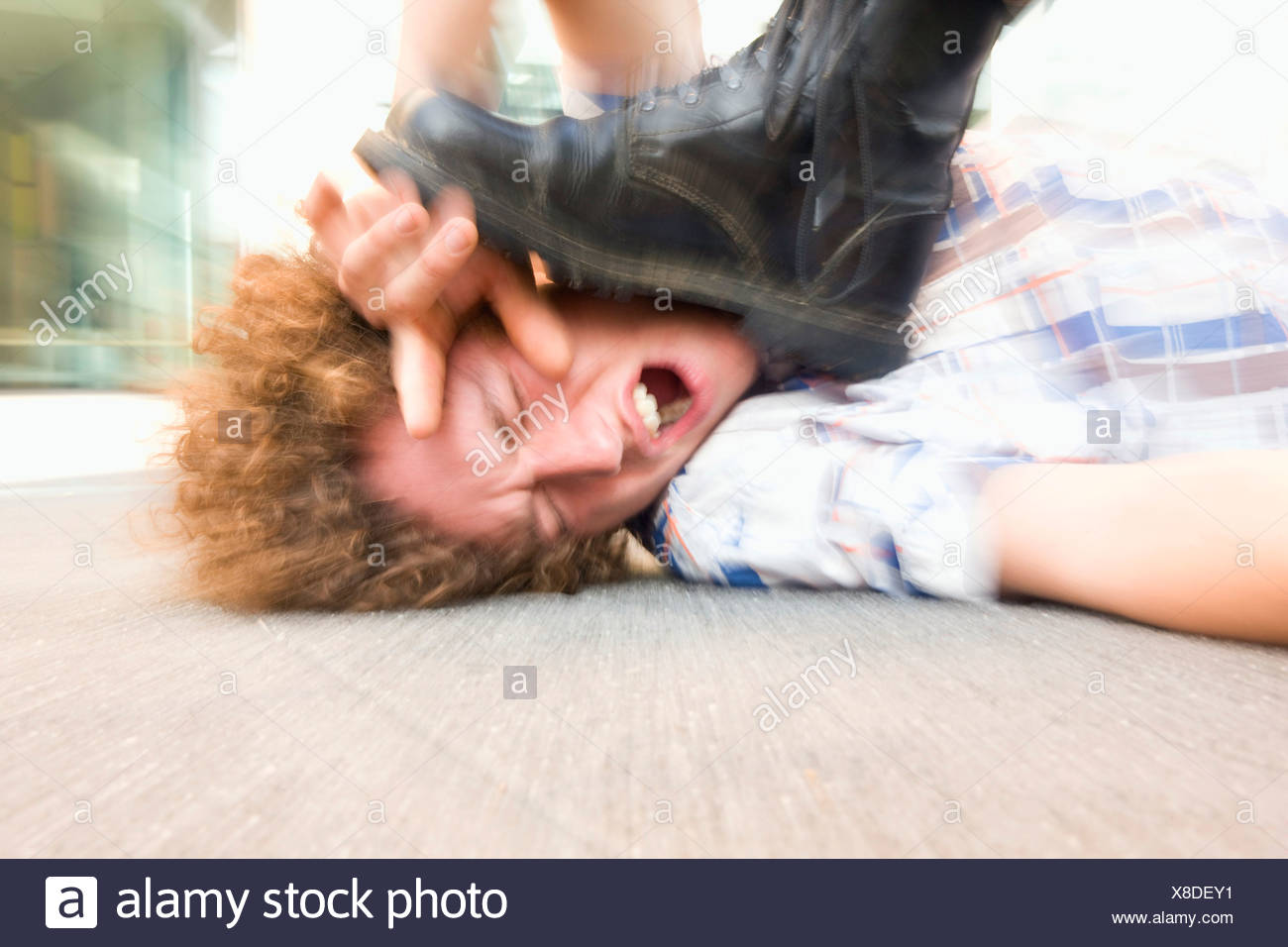Young man lying on ground being stepped on by someone
