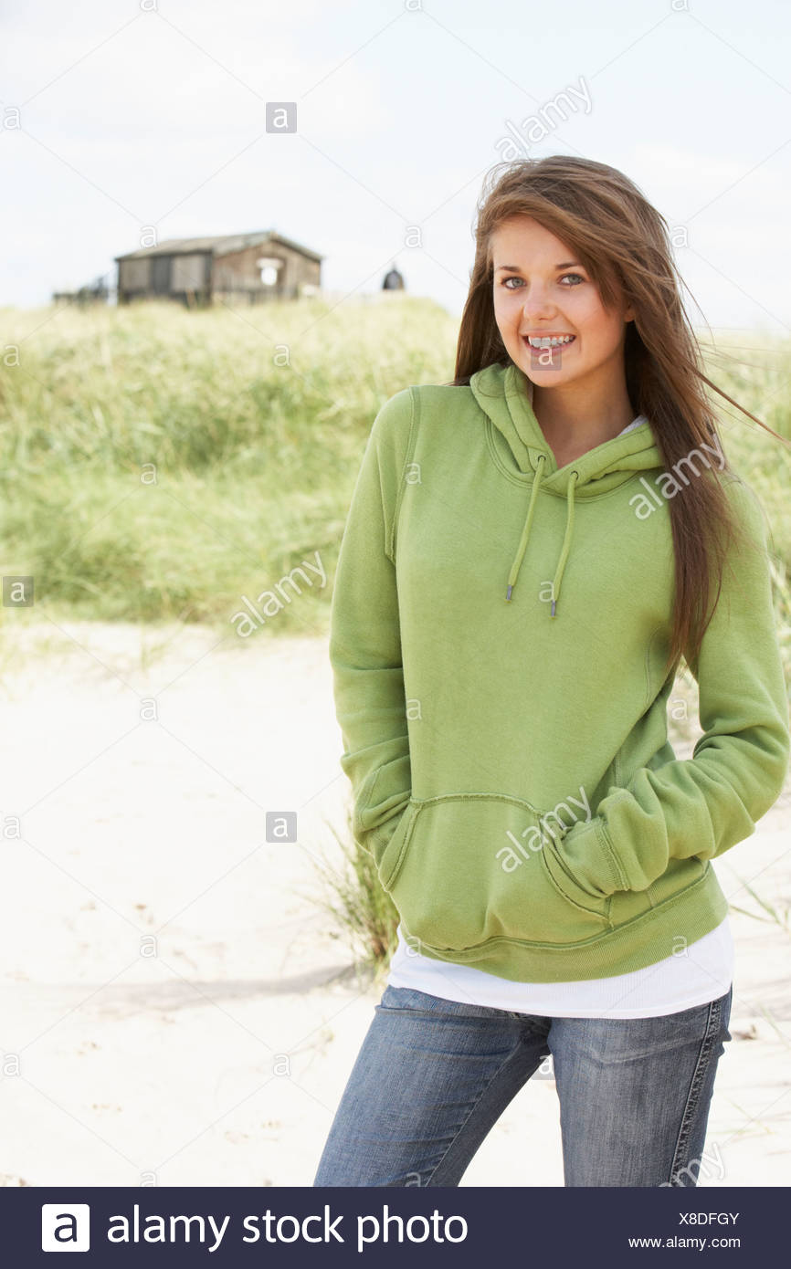 Young Woman Standing On Beach Wearing Hooded Top With Old Beach Hut In Distance - Stock Image