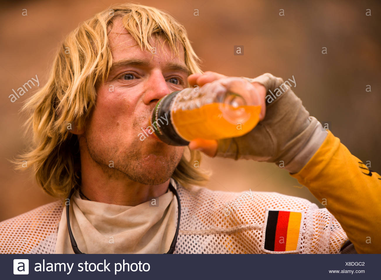 Man drinking an energy drink during an adventure race near Moab, Utah. - Stock Image