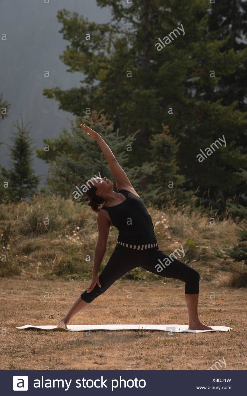 Fit woman performing stretching exercise on an open ground - Stock Image