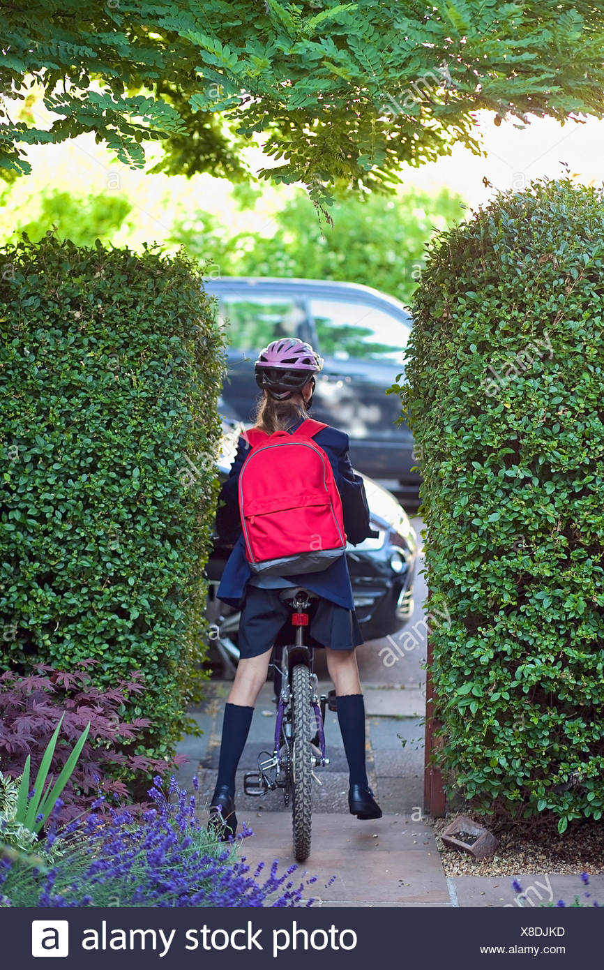 Young girl (12-13) going to school on bike - Stock Image