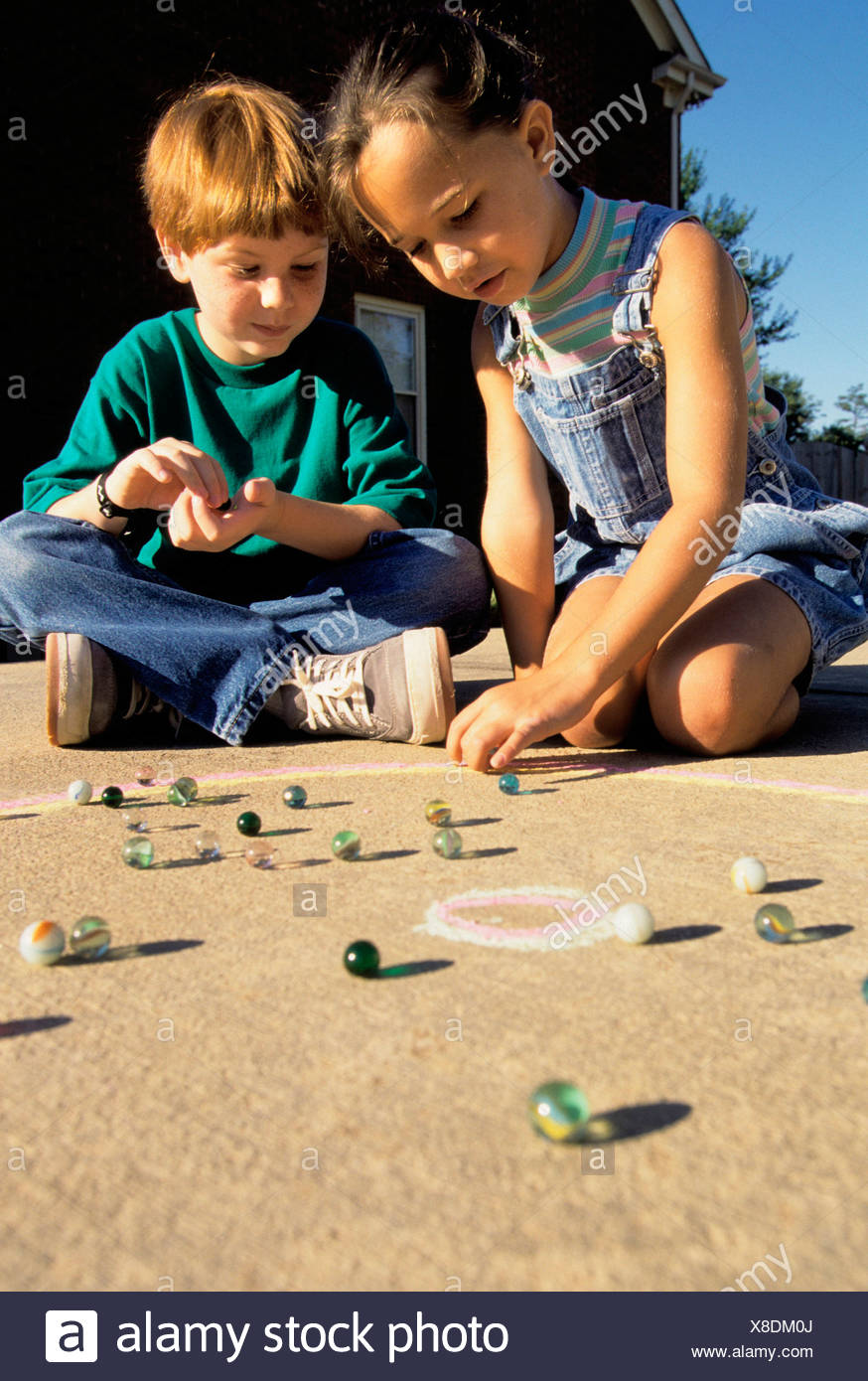 Kids playing with marbles. - Stock Image