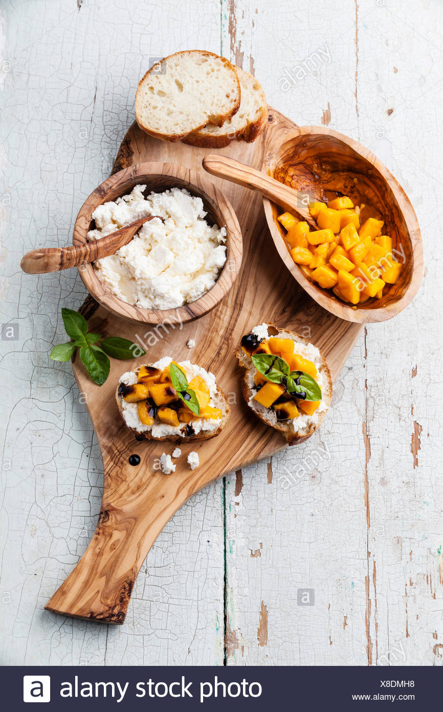 Bruschetta with chopped mango, basil and goat cheese on fresh baguette - Stock Image