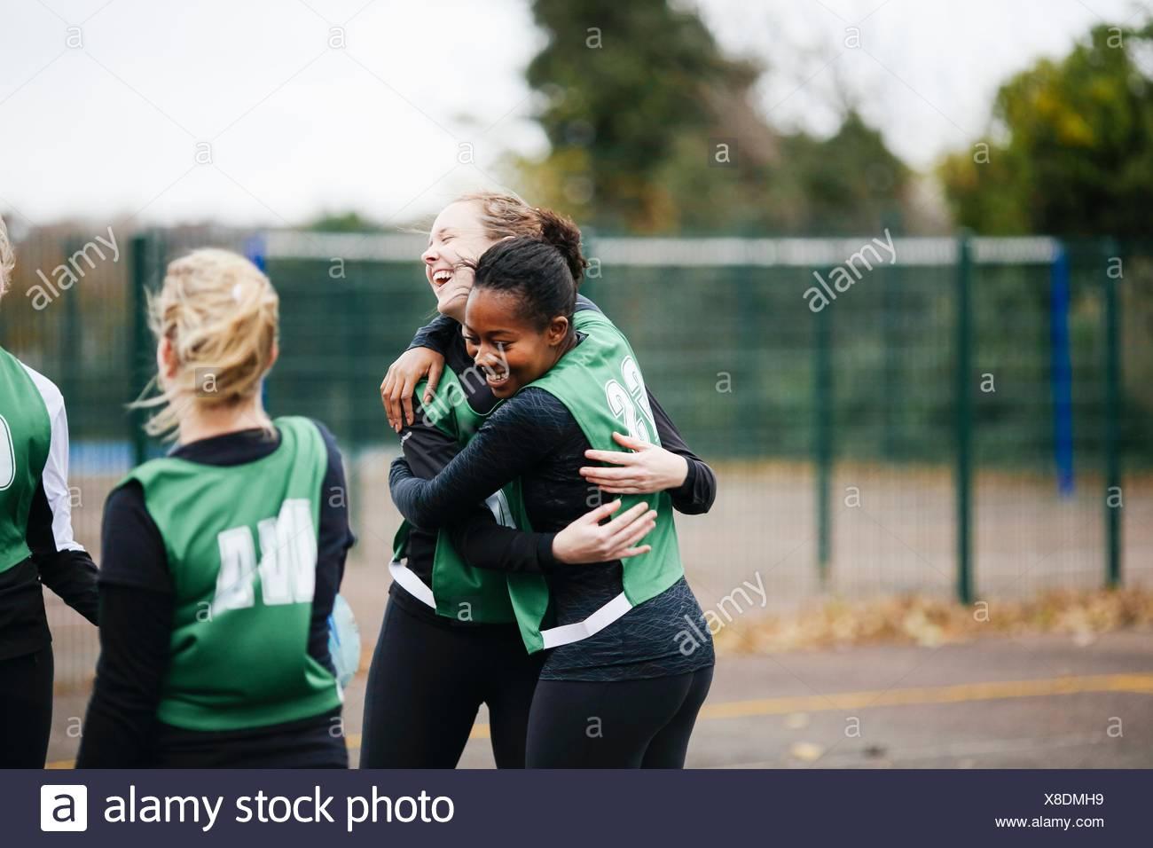 Happy female netball team celebrating win on netball court - Stock Image