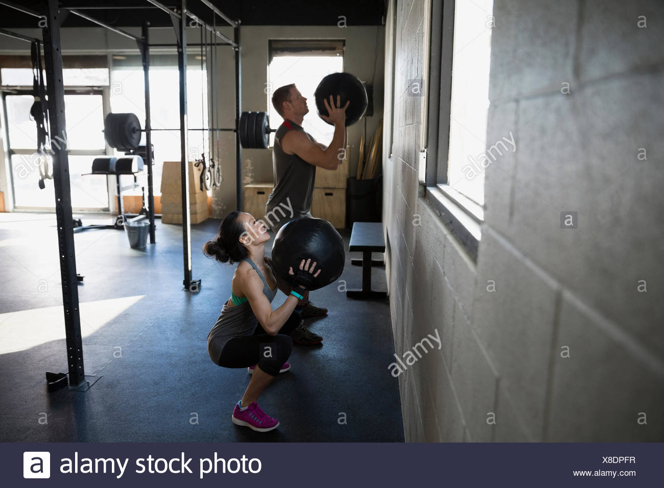 Man and woman squatting with medicine balls gym - Stock Image