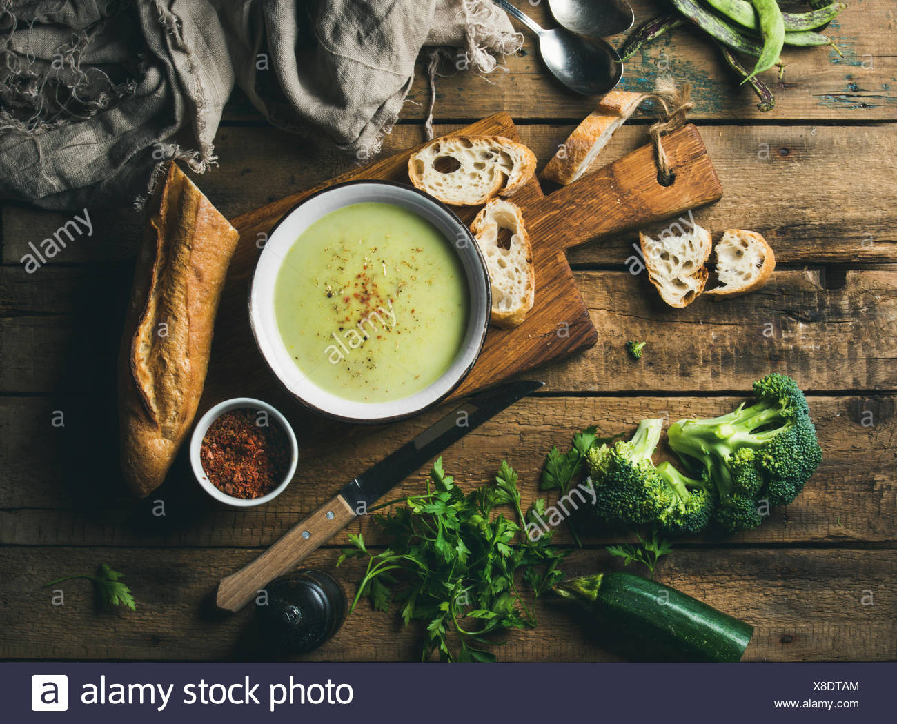 Homemade pea, broccoli, zucchini cream soup in white bowl with fresh baguette on wooden board over rustic background, top view, - Stock Image
