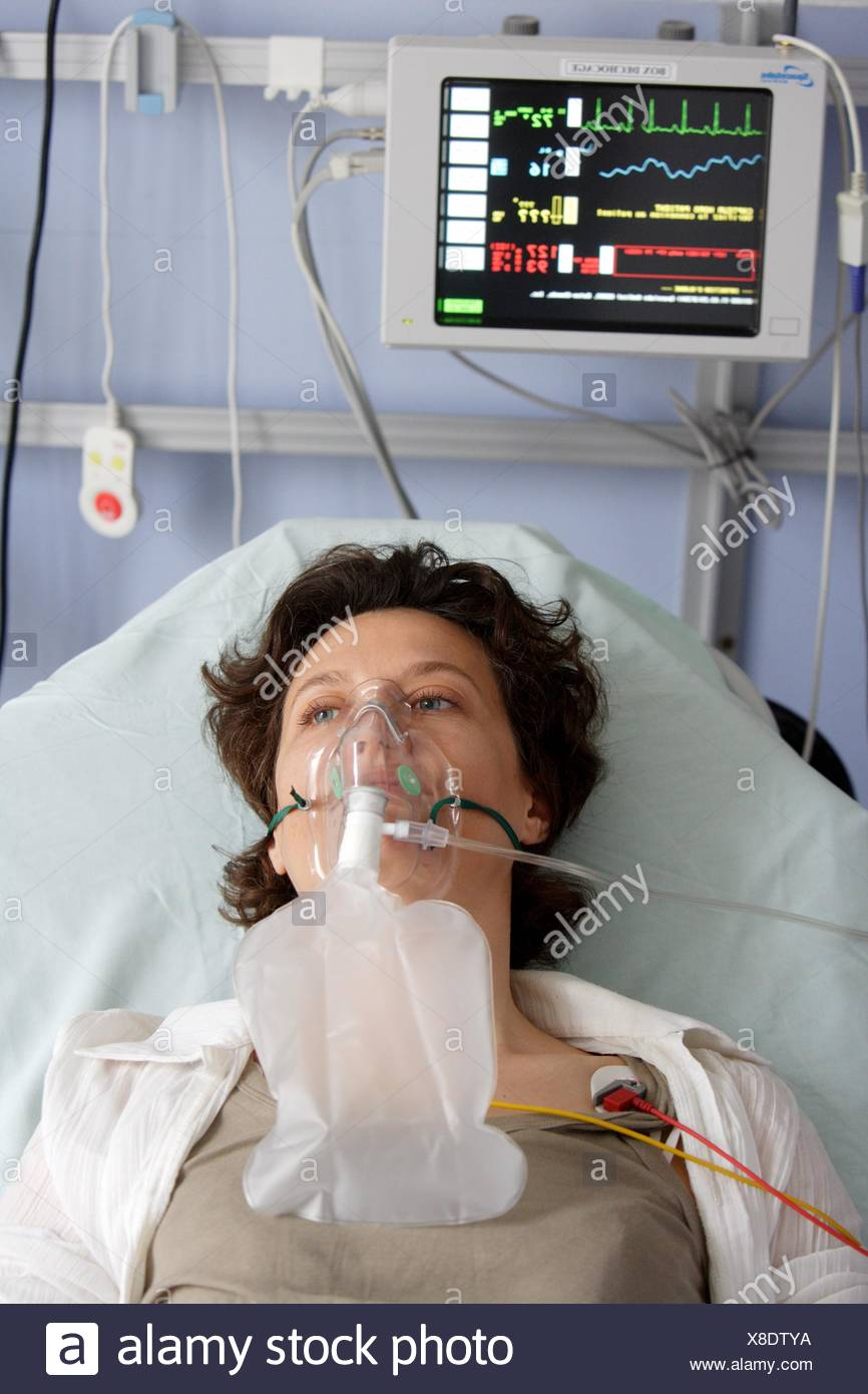 Patient with oxygen mask for respiratory assistance at emergency department. - Stock Image