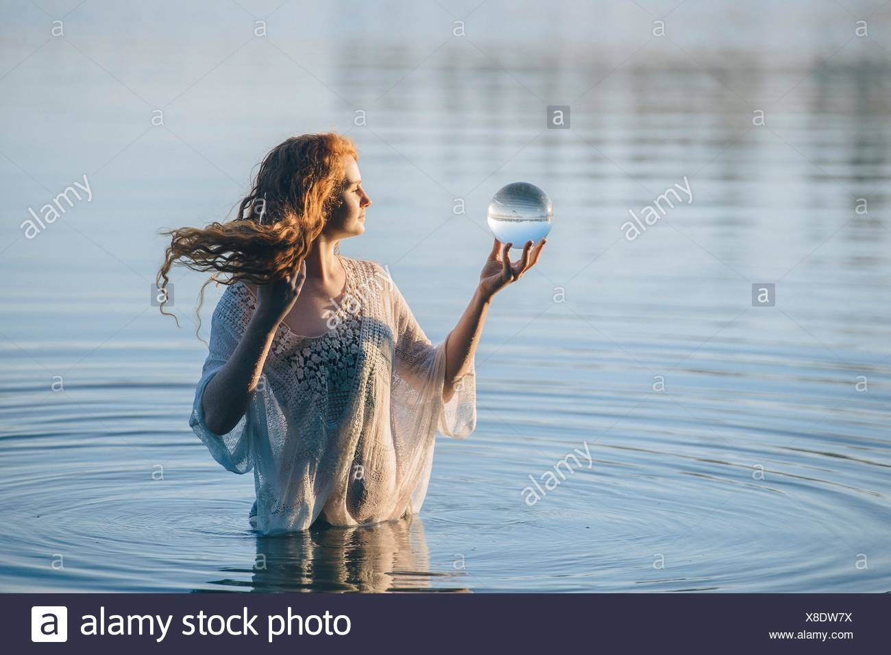 Young woman with long red hair standing in lake gazing at crystal ball - Stock Image