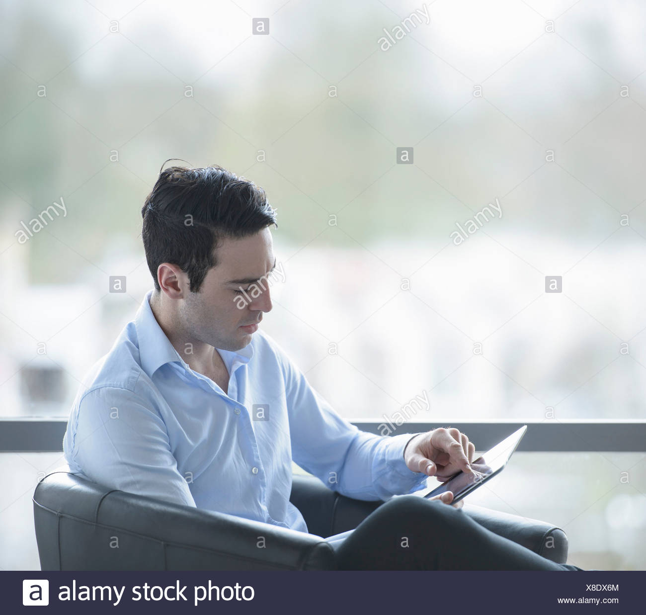 Businessman using digital tablet by window of office - Stock Image
