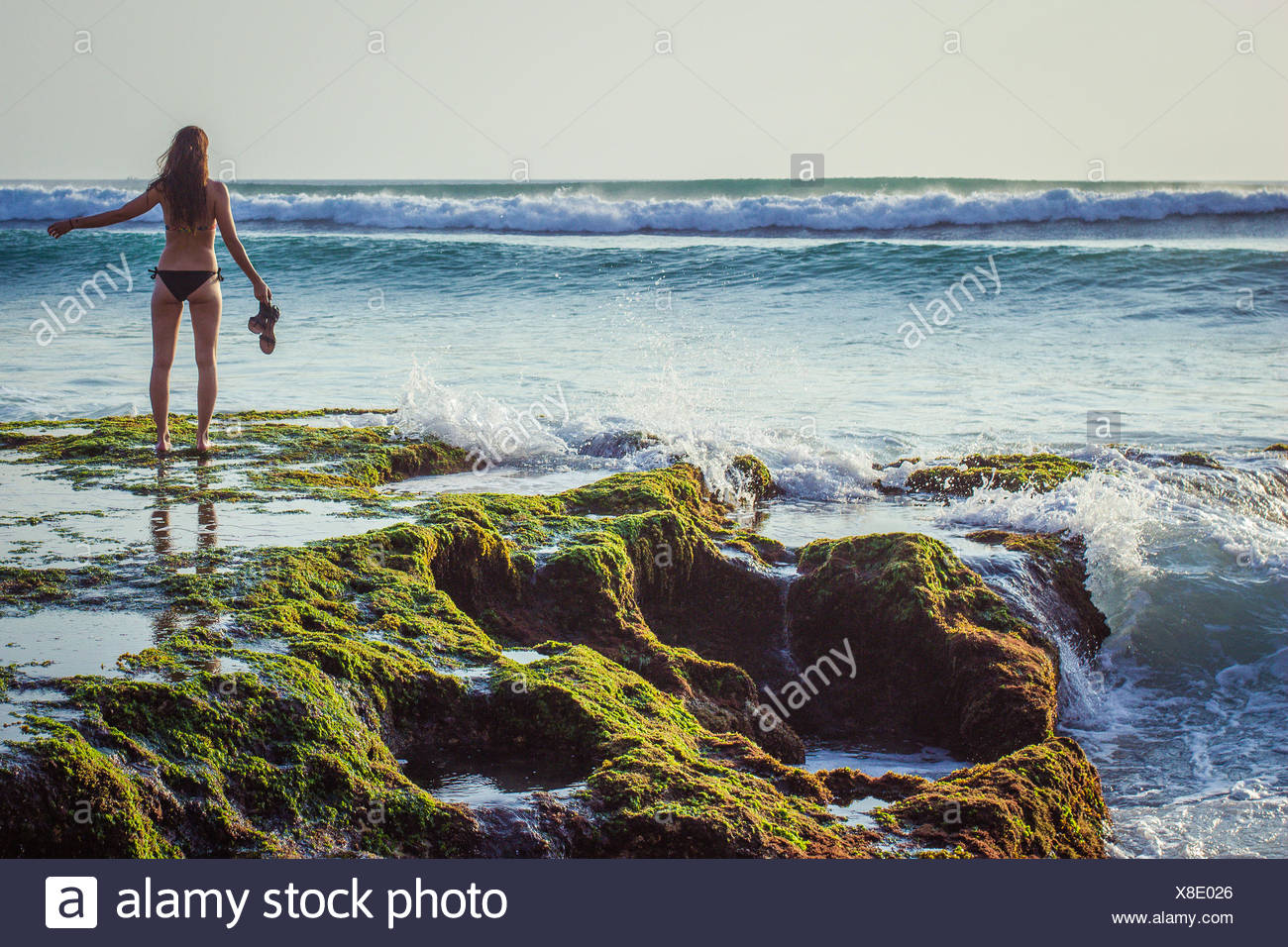 Indonesia, Bali, Woman standing in front of sea - Stock Image
