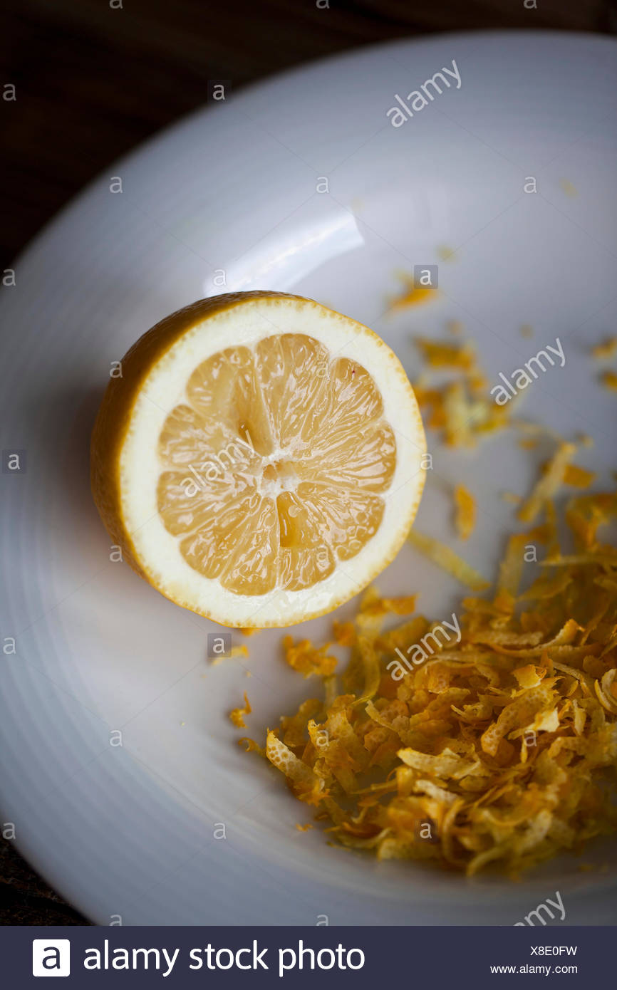 Half of lemon and grated lemon zest on a white plate - Stock Image