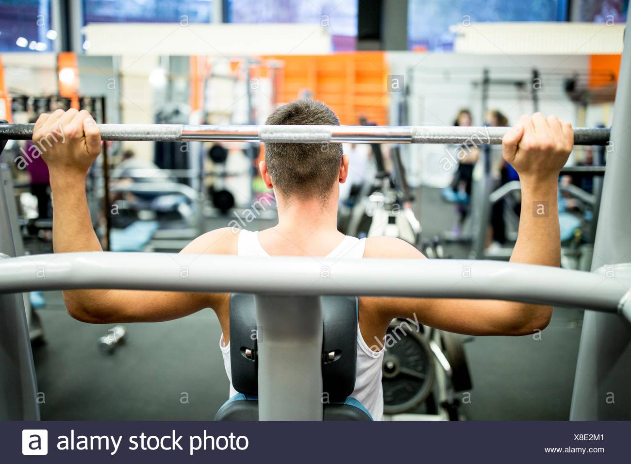 PROPERTY RELEASED. MODEL RELEASED. Young man using exercising machine in gym. - Stock Image