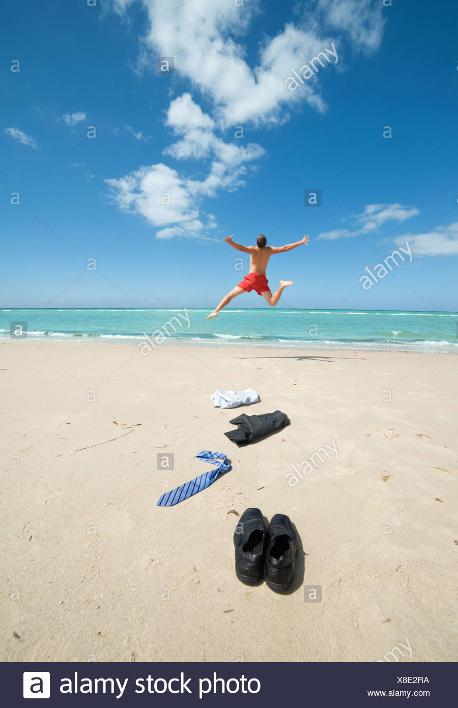 businessman jumping on the beach Stock Photo