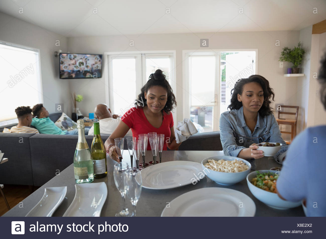African American teenage sisters eating in kitchen Stock Photo