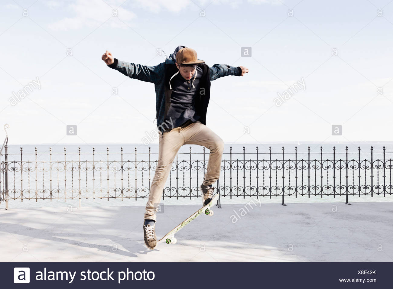 Germany, Schleswig Holstein, Teenage boy jumping with skateboard - Stock Image