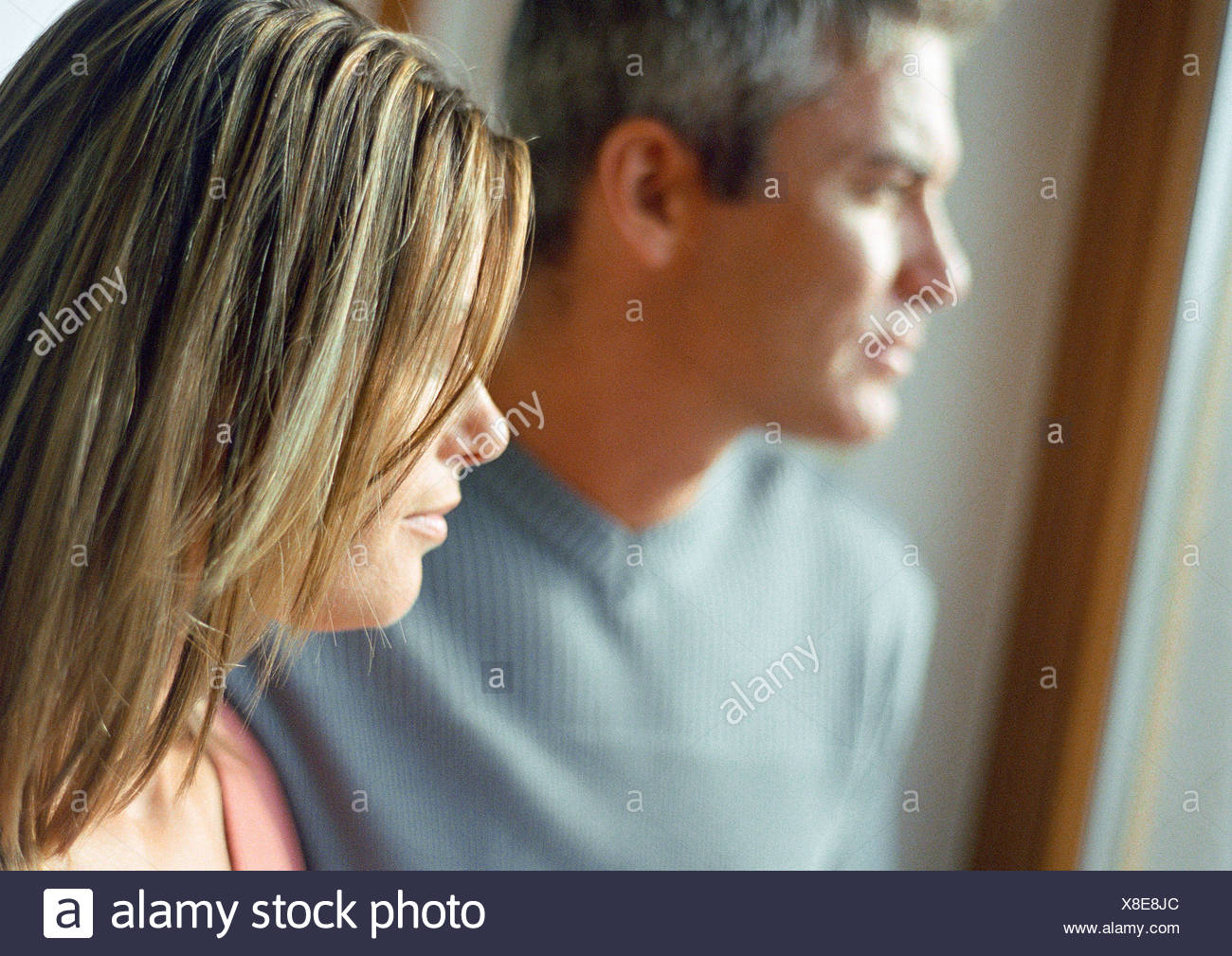 Man and woman, side view, head and shoulders, natural light on faces, close-up - Stock Image