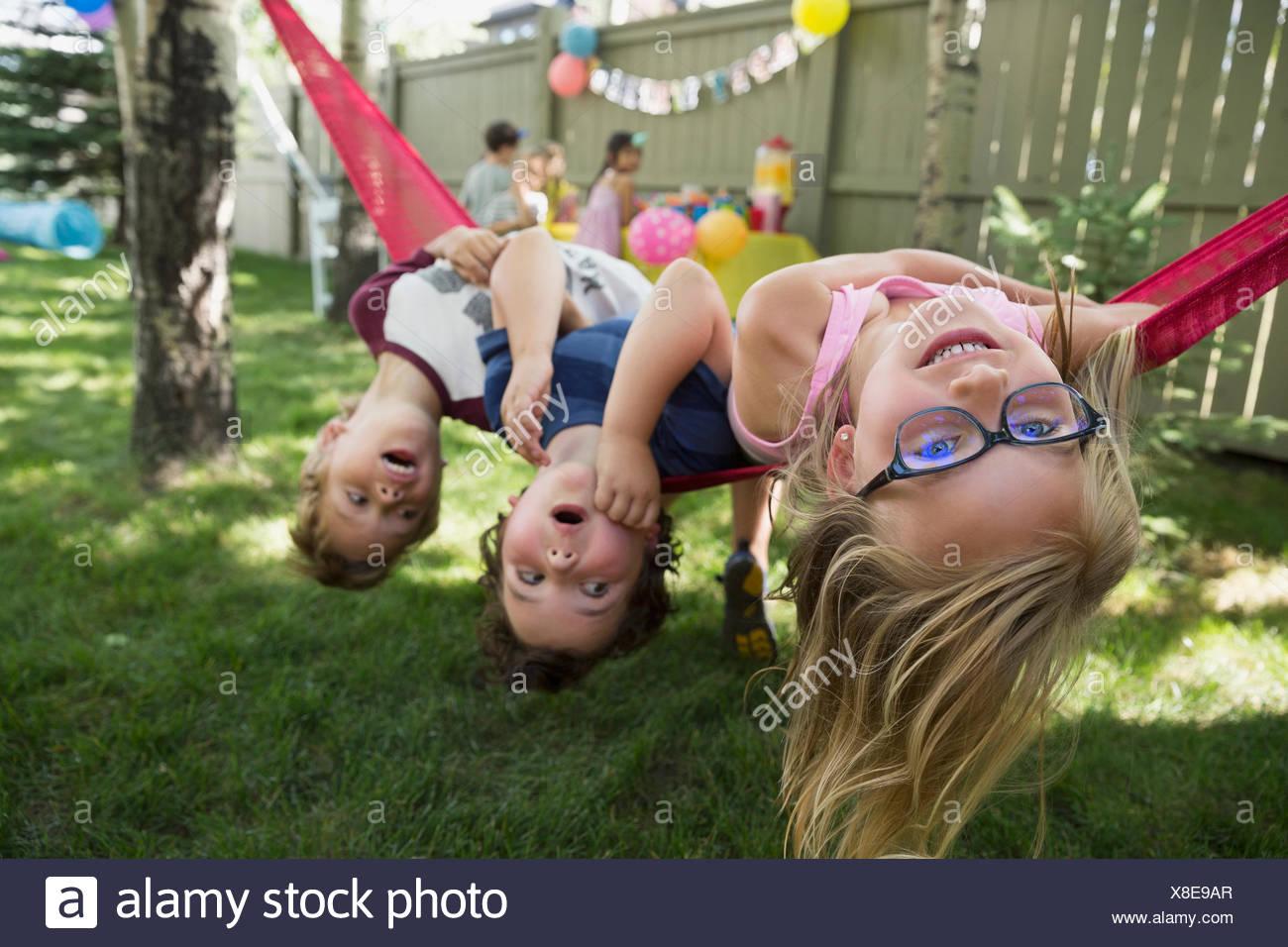 Portrait upside-down kids hammock backyard birthday party - Stock Image