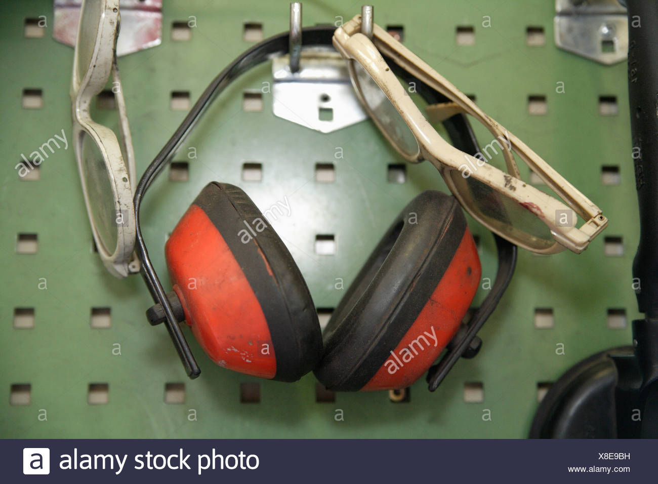 Germany, Ebenhausen, Close up of safety glasses and ear protectors on pegboard in repair garage - Stock Image